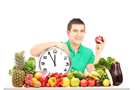 Young man holding a wall clock and apple, sitting on a table full of fruits and vegetables, isolated on white background photo