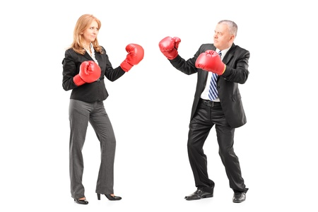 stance: Full length portrait of a mature businessman and businesswoman with boxing gloves, isolated on white