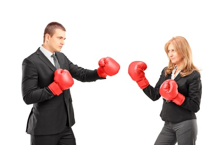 Businesswoman with boxing gloves having a fight with a businessman isolated on white background photo