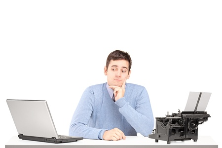 Confused man sitting on a desk with a laptop and a typing machine isolated on white background photo