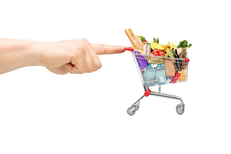 Finger pushing a shopping cart full of food products, isolated on white background photo