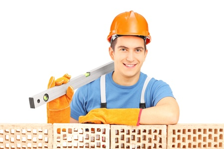 Male construction worker holding a bubble level and resting on a brick wall isolated on white background photo