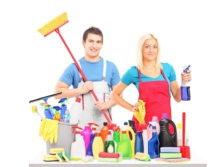 orden y limpieza: Limpiadores de hombres y mujeres posando con las fuentes de limpieza en una mesa aislada en el fondo blanco Foto de archivo