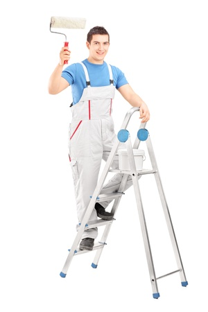 climb job ladder: Full length portrait of a male painter holding a roller and standing on a ladder isolated on white background