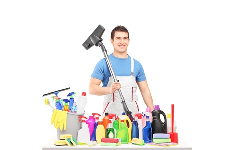 hover: Male cleaner holding a hover and posing with cleaning supplies isolated on white background