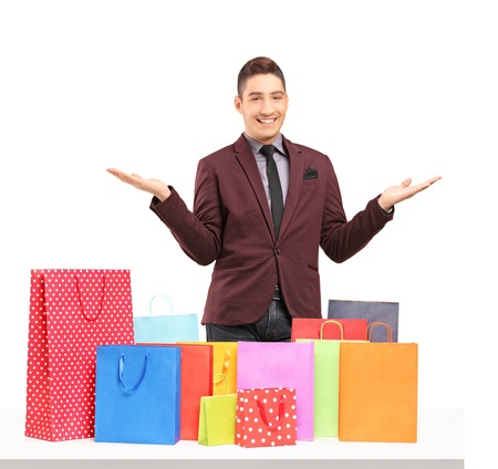 gift bags: Satisfied young man posing with plenty of shopping bags on a table isolated on white background