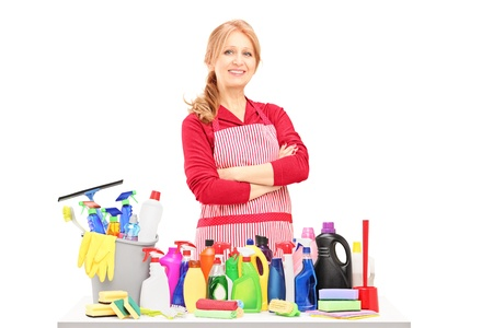 housecleaning: Smiling woman posing with cleaning supplies on a table isolated on white background