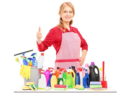 Woman posing with cleaning supplies and giving a thumb up isolated on white background photo