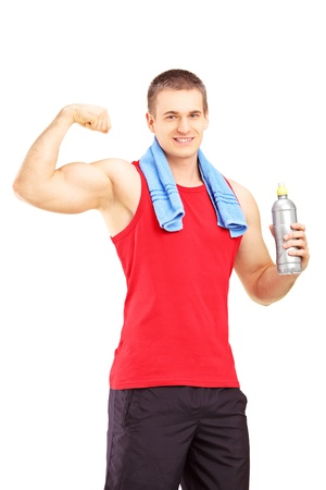 Athletic young male in sportswear showing his muscles and holding a water bottle isolated against white background photo