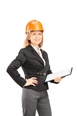 Female engineer with a helmet holding a clipboard and posing isolated on white background Stock Photo - 18522684