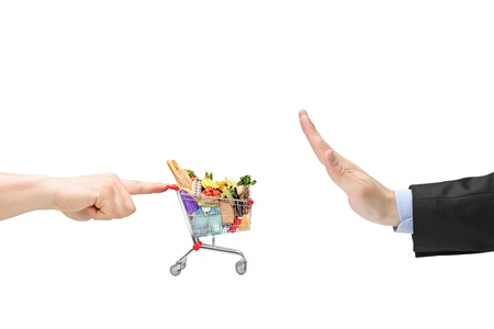 Finger pushing a shopping cart with food products and male hand gesturing stop isolated on white background photo