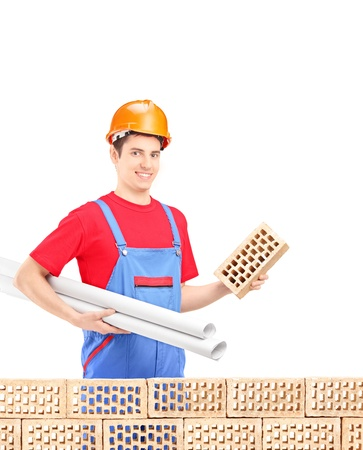 Male engineer with helmet holding a brick and blueprints behind a wall brick Stock Photo - 18522690