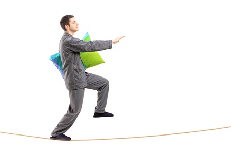 sleepwalking: Full length portrait of a young man holding a pillow and sleepwalking on a rope isolated against white background