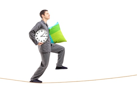 sleepwalking: Full length portrait of a young man with a pillow and clock sleepwalking on a rope isolated against white background