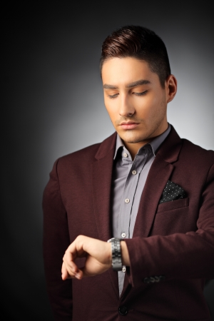 looking at watch: Handsome young man checking the time on his wrist watch