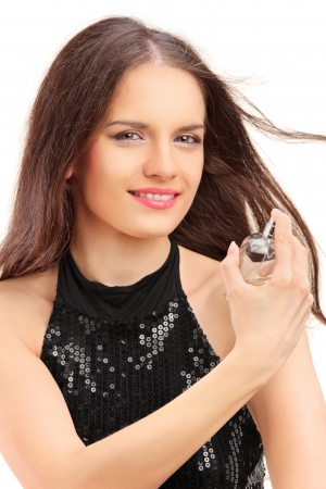 Portrait of a beautiful young female spraying a perfume isolated on white background photo