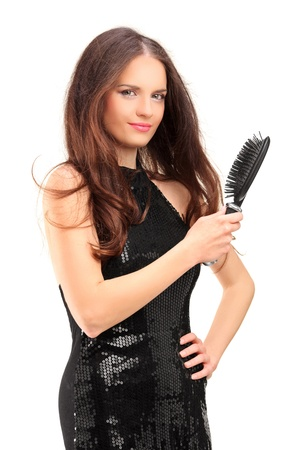 hair brush: Pretty young woman holding a hair brush isolated on white background