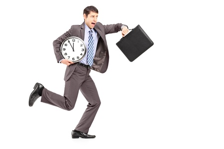 late 20s: Full length portrait of a young businessman running late with a clock and a briefcase isolated on white background Stock Photo