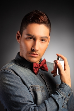 A portrait of a handsome male applying perfume and looking at camera photo