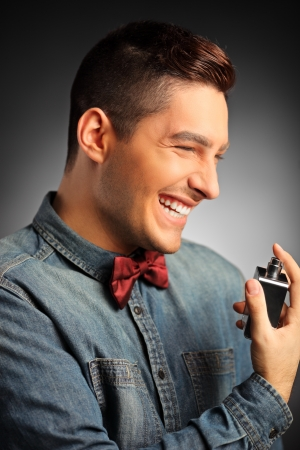 A portrait of a smiling handsome male applying perfume photo