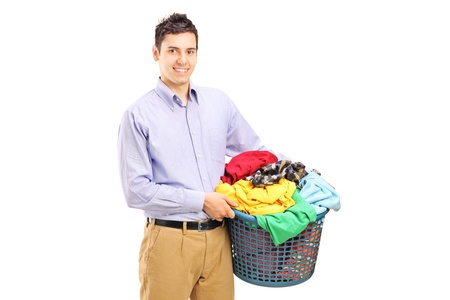 A smiling man holding a laundry basket isolated on white background photo