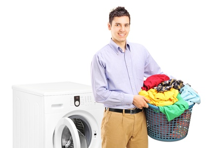 A smiling man with laundry bin posing next to a washing machine isolated on white background photo