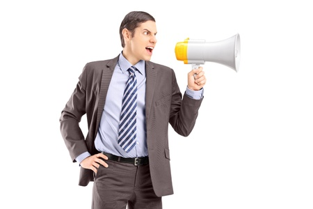 An angry young businessman announcing via megaphone isolated against white background Stock Photo - 18624408