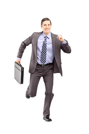 late 20s: Full length portrait of a businessman running with a briefcase and looking at camera isolated on white background
