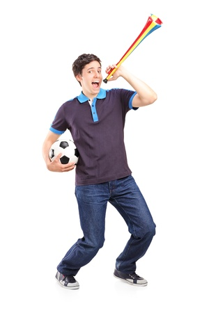 Full length portrait of a male sport fan holding a football and horn isolated on white background photo