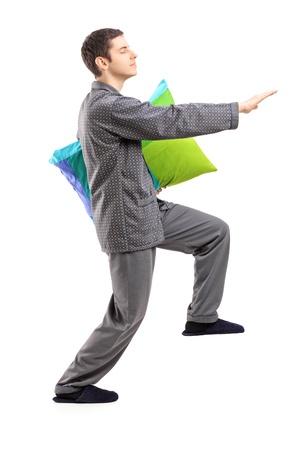pijama: Retrato de cuerpo entero de un hombre en pijama sonambulismo con una almohada en la mano aisladas sobre fondo blanco Foto de archivo