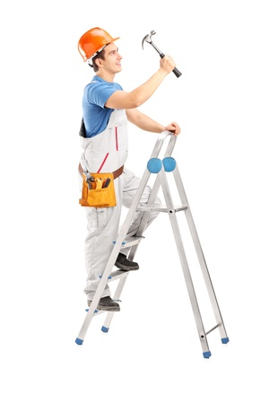 Full length portrait of a repairman on a ladder working with a hammer isolated on white background