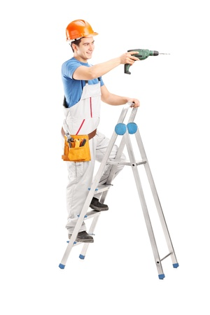 Full length portrait of a repairman with a drilling machine on a ladder isolated on white background photo