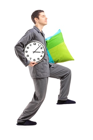 sleepwalker: Full length portrait of a sleepwalker with a pillow and a clock isolated on white background