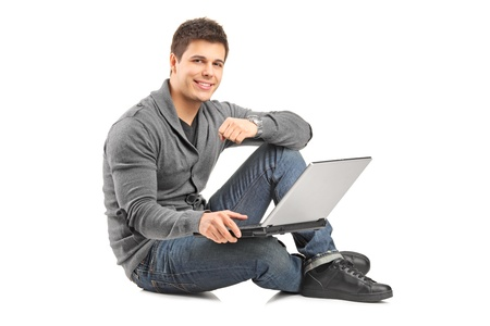 Handsome guy working on a laptop and sitting on a floor, isolated against white background