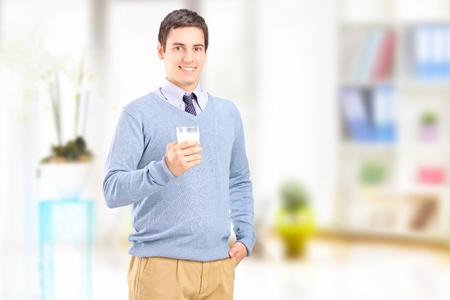 Man posing with a glass of milk at home photo