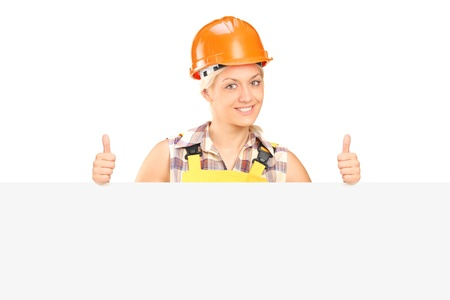 Young female with helmet posing behind a panel with thumbs up isolated on white background photo