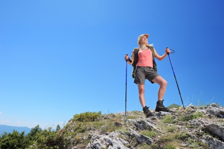 A young  woman with backpack and hiking poles posing in mountain photo