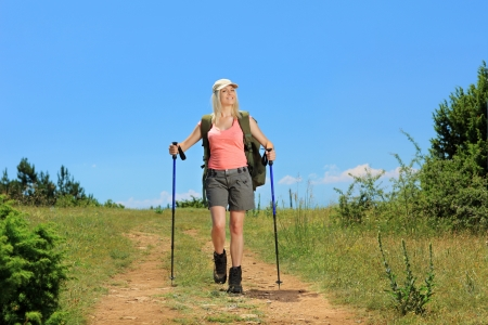 A young woman with backpack and hiking poles walking in the mountain photo