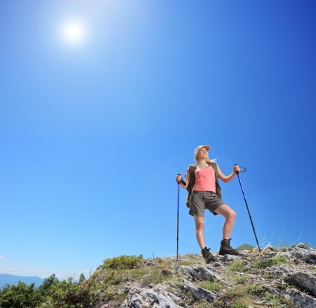 Young female with backpack and hiking poles posing at sunny day in mountain photo