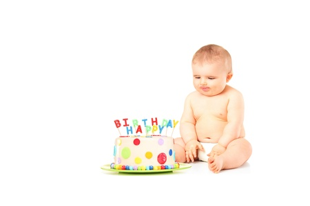 A 9 months old baby in diapers sitting next to a birthday cake isolated against white background  photo