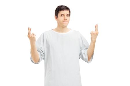 hospital gown: A male patient in a hospital gown with fingers crossed posing isolated on white background