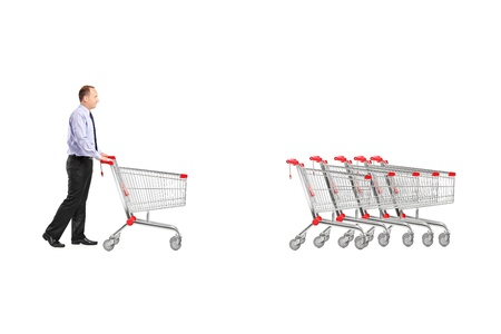 returning: Full length portrait of a man returning an empty shopping cart isolated on white background