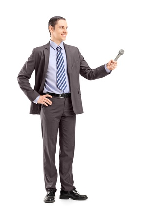 medium length: Full length portrait of a professional male reporter holding a microphone, isolated on white background
