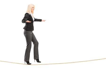 Full length portrait of a young woman walking on a rope, isolated on white background photo