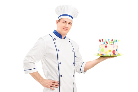 Young male chef in a uniform holding a decorated birthday cake isolated on white background photo