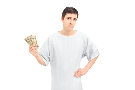 recovering: A sad male patient in a hospital gown holding US dollars, isolated on white background