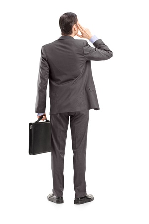 Full length portrait of a businessman thinking, shot from behind, isolated against white background photo