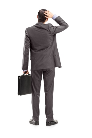 Full length portrait of a businessman with briefcase, holding his head, shot from behind, isolated on white background photo