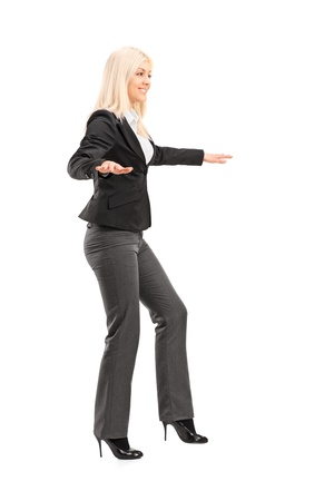 Full length portrait of a businesswoman trying to keep balance, isolated on white background photo