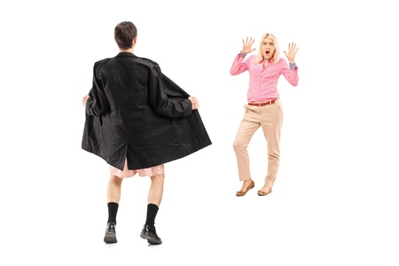 overcoat: Full length portrait of a flasher scaring a young woman, isolated on white background Stock Photo